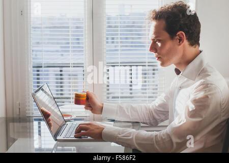 Businessman la lecture de courriers électroniques dans le bureau avec tasse de café Banque D'Images