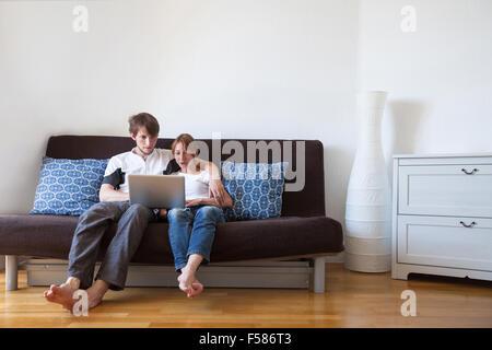 Jeune famille à l'aide d'ordinateur portable à la maison, en couple sur le canapé avec ordinateur Banque D'Images