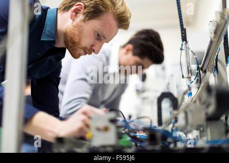 Deux beaux jeunes ingénieurs travaillant sur des composants électroniques et puces cassées de fixation