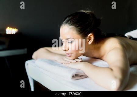 Portrait d'une jeune et belle femme reposant, avec les yeux ouverts sur une table de massage dans une pièce sombre Banque D'Images