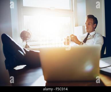 D'affaires exécutif blanc homme assis à son bureau de l'inspiration et la pensée Banque D'Images