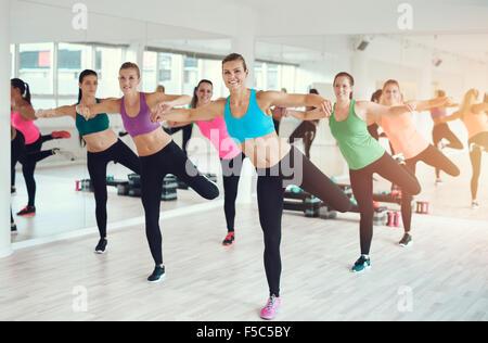 Grand groupe de mettre en place des jeunes femmes travaillant dans une salle de sport faire des exercices d'aérobic Banque D'Images
