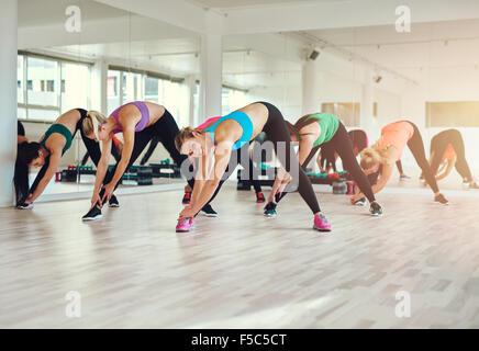 Groupe de femmes de chiffons colorés dans une salle de sport faisant de l'aérobic ou l'échauffement avec des exercices Banque D'Images