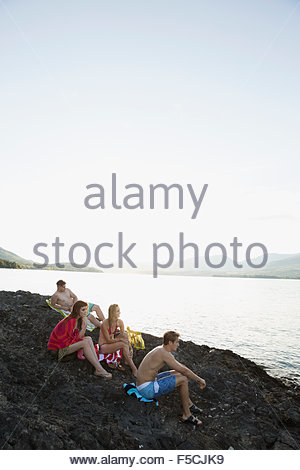 Jeunes amis se détendre sur des pierres à Lakeside Banque D'Images