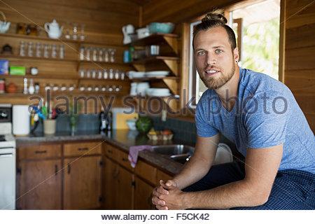 Portrait jeune homme assis dans la cuisine cabine Banque D'Images