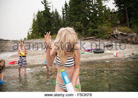 Famille ludique avec des pistolets à eau dans le lac Banque D'Images
