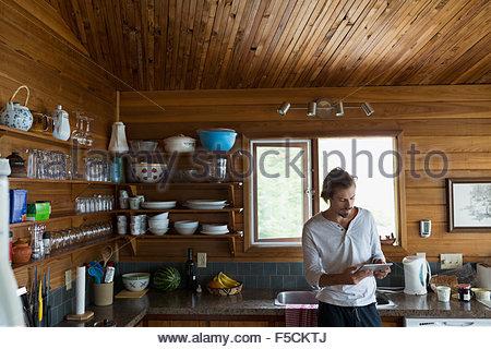 Man using digital tablet in cuisine cabine Banque D'Images