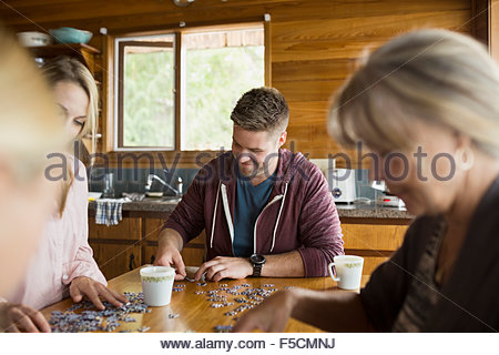 Multi-generation family assemblage jigsaw puzzle table cabine Banque D'Images