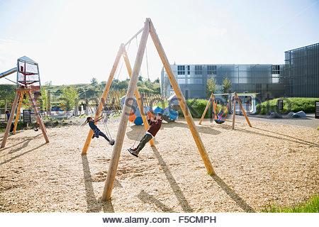 Les enfants jouant sur les balançoires à aire ensoleillée Banque D'Images