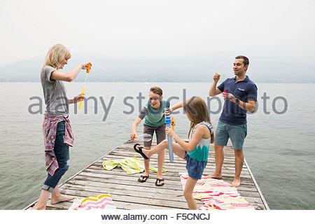 Famille jouant avec des bulles sur lake dock Banque D'Images