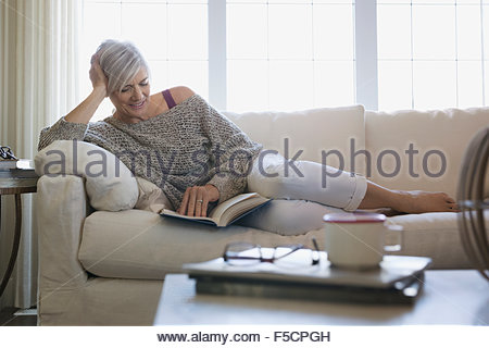 Woman Reading book et relaxing on sofa Banque D'Images