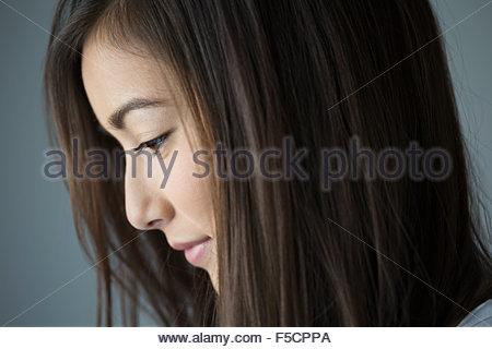 Close up profile pensive brunette woman looking down Banque D'Images