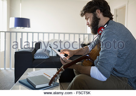 L'homme avec l'enregistrement de guitare music with digital tablet Banque D'Images