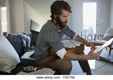 L'homme avec l'enregistrement de guitare music with digital tablet Banque D'Images