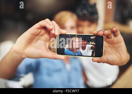 Deux jeunes femmes prenant un amis sur un mobile avec selfies l'image affichée à l'appareil photo sur l'écran, jeune Banque D'Images