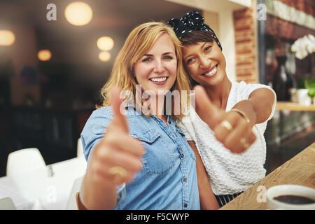 Deux heureux young female friends donnant un coup de geste d'approbation et le succès qu'ils siègent dans les bras Banque D'Images