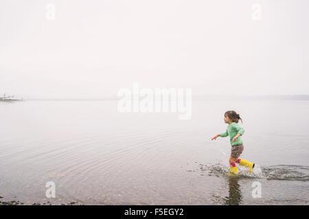 Fille qui court dans un lac avec des bottes wellington