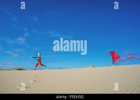 Enfant volant red kite on sandy beach Banque D'Images