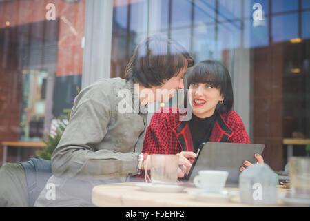 Couple de jeunes beaux caucasian man et woman business collègue assis sur un bar à l'aide de tablet et smartphone Banque D'Images