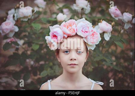 Jeune fille portant un chapeau avec des roses Banque D'Images
