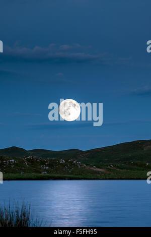 Supermoon passant au-dessus d'un lac sur la montagne Banque D'Images