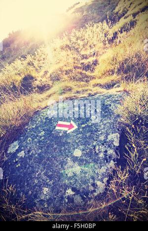 Sentier stylisé rétro panneau de flèche contre le coucher du soleil avec l'effet lens flare.