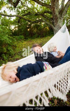 La Suède, Gotland, Havdhem, grand-mère et ses petits-enfants (2-3, 4-5) en hamac Banque D'Images