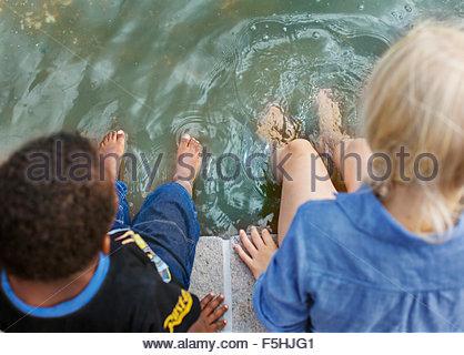 Danemark, copenhague, Frederiksberg, Girl (10-11) and boy (4-5) sitting avec pieds dans l'eau Banque D'Images