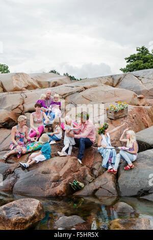 La Suède, l'Uppland, Roslagen, Big family having picnic sur les rochers au bord de mer Banque D'Images