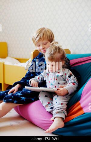 La Suède, Boy (10-11) et une fille (2-3) à l'aide de tablet Banque D'Images