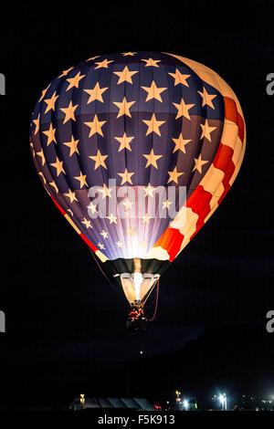 Allumé Stars and Stripes hot air balloon flying Dawn Patrol, Albuquerque International Balloon Fiesta, Nouveau Mexique Banque D'Images