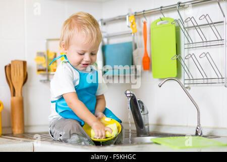 Enfant mignon garçon 2 ans lave-up dans la cuisine Banque D'Images