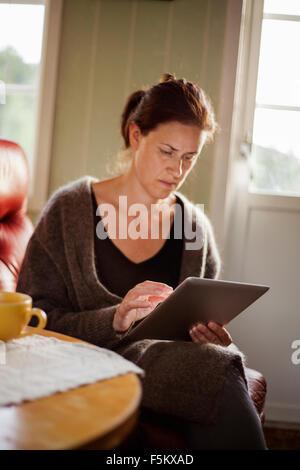 Mid-adult woman using digital tablet
