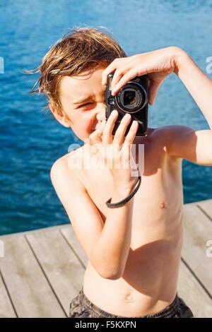 La Suède, l'Uppland, Runmaro Barrskar,, Portrait de garçon (6-7) photographing on jetty Banque D'Images