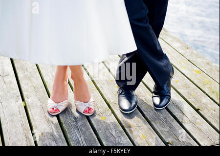 La Suède, l'Uppland, Arholma, les pieds de l'homme et de la femme debout sur la jetée en bois Banque D'Images