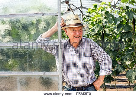 Senior man wearing hat appuyé contre la porte de hothouse looking at camera smiling Banque D'Images