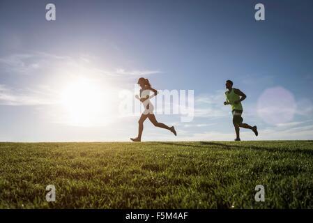 L'homme soleil et woman running in park Banque D'Images