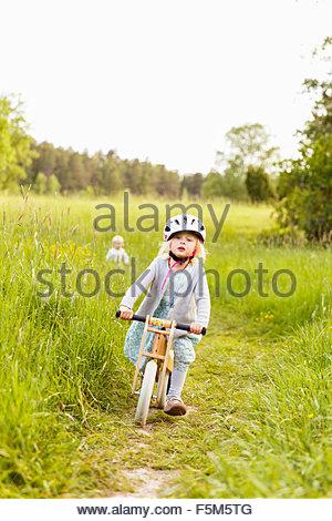 La Suède, Sodermanland, Nacka, Girl (4-5) on bicycle in park et boy (2-3) en arrière-plan Banque D'Images