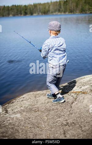 La Suède, Varmdo, archipel de Stockholm, Boy (4-5) d'essayer de prendre du poisson Banque D'Images