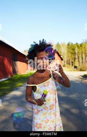 La Suède, Vastra Sweden, Runnas Gullspang, Girl (6-7) soufflant des bulles de savon Banque D'Images