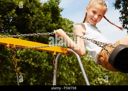 Girl with pigtails sur swing smiling at camera Banque D'Images
