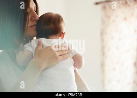 Maman de transporter dans la chambre de bébé Banque D'Images