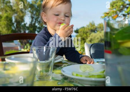 Female toddler eating at table outdoors Banque D'Images