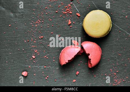 Certains macarons appétissants de saveurs différentes sur une surface en ardoise Banque D'Images