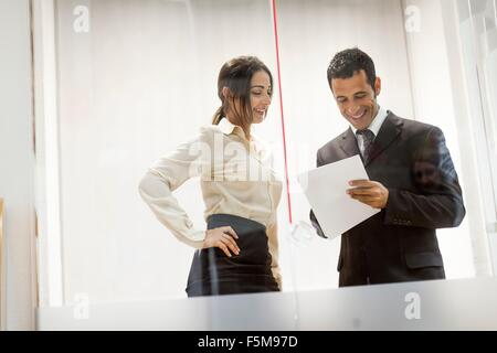 Businessman and businesswoman looking at documents, avoir conversation Banque D'Images
