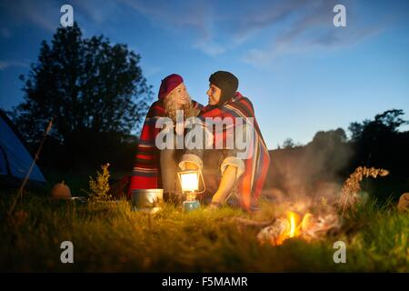 Young couple sitting by camping Camp au crépuscule Banque D'Images