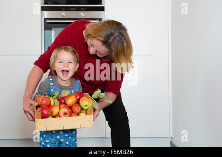 Portrait of female toddler et mother holding caisse de pommes dans la cuisine Banque D'Images