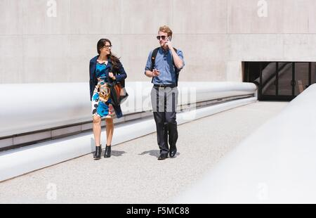 Businessman and woman walking and talking in city Banque D'Images