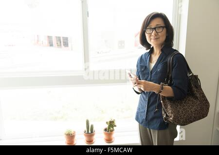 Mature Woman standing in front of window holding smartphone smiling at camera Banque D'Images