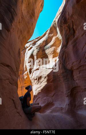 Une femme admire la lumière chaude dans le Ravin de Peekaboo Escalante Canyons de Grand Staircase Escalante National Banque D'Images